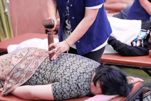 Thai massage by hammering part of the body to restore the energy flow